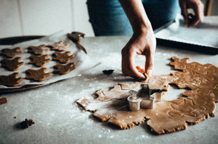 person making gingerbread cookies